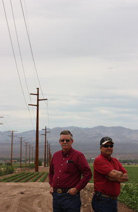 Electric Coop managers in front of the power transmission lines