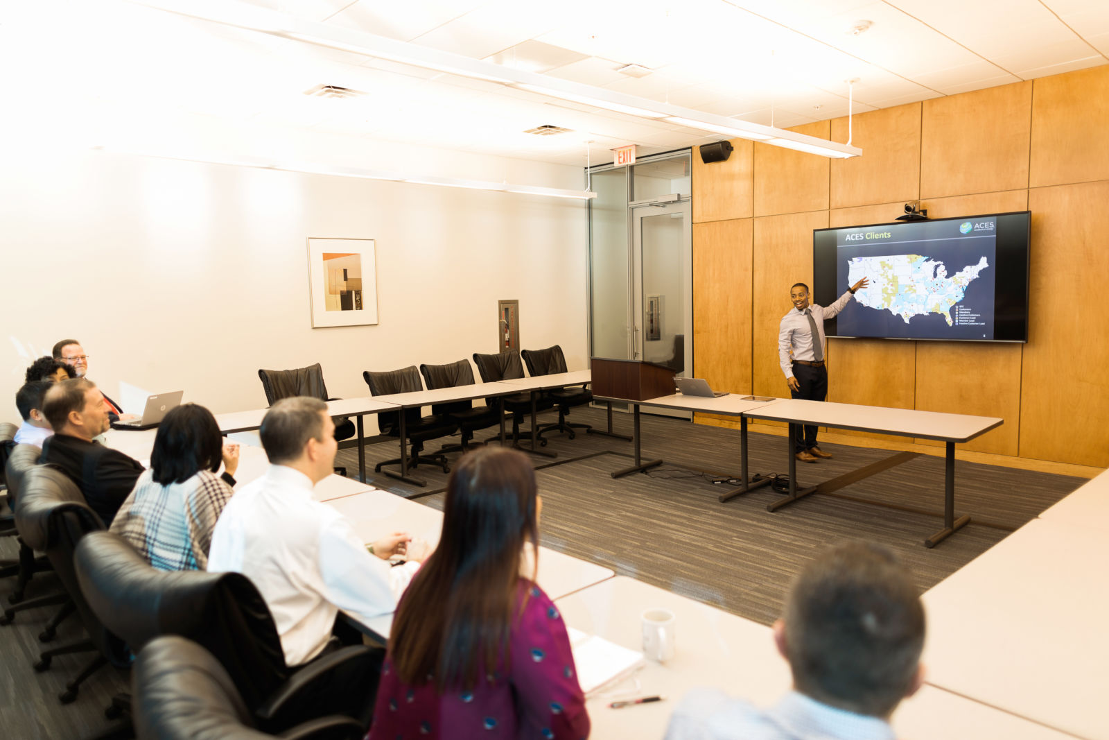 a presenter shows a slide on a TV screen to a group of people sitting at a table