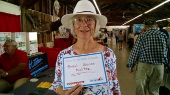 "Woman holding a sign reading: ""I'm a co-op voter because… Rural Voices Matter. #coopsvote. Co-Ops Vote."""